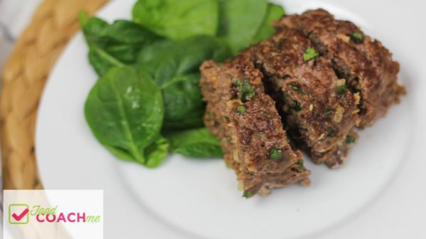 Low carb meatloaf beef and onion with chopped spinach on a white plate