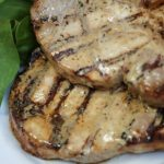 Bone in pork chops brushed with light Caesar dressing and grilled
