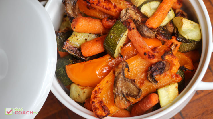 Oven roasted vegetables orange bell pepper zucchini carrots mushrooms in a white dish