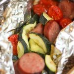 Turkey Sausage and Veggies foil packets with turkey kielbasa sausage zucchini and cherry tomatoes in foil on the grill
