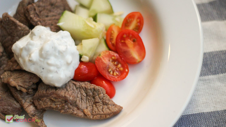 Greek steak bowl with thinly sliced sirloin steak, Greek seasoning, tzatziki sauce, cucumber and tomatoes